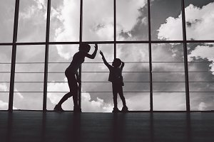 Silhouette of mother and daughter in the gym