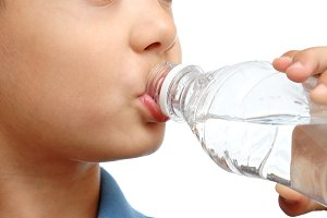 Boy drinks water from bottle