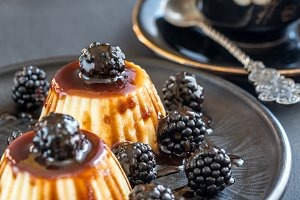 Vanilla puddings with blackberries