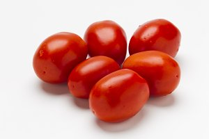 Red plum tomatoes on a white background