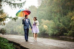 Happy Bride and groom at wedding walk with color umbrella