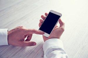 man's hands using smartphone