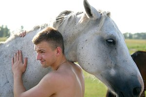 Young handsome man embracing and stroking white horse outdoors. Guy hugging a horse in the field, he caresses and petting the stallion. Love to the animals. Close-up