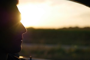 Profile of young handsome man drives a car at sunset. Guy driving the car under sunset sky at outdoor. Boy inside his car. Summer time. Close-up.