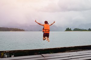 woman jumping from jetty to lake