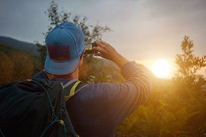 Hip backpacker taking a photo of sunset on his smartphone