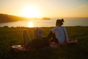 young hip couple looking at sunset from  hill over sea