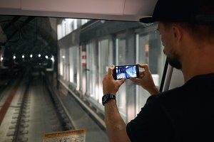 Young man taking a photo of an underground tunnel