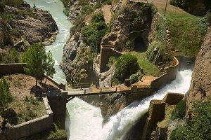 Bridge over a waterfall among green hills