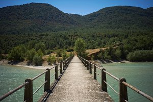 Concrete pedestrian bridge over a bay among green hills