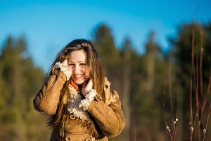 Young joyful nice blond woman clothed sheepskin coat and scarf.  Girl is enjoying a warm sunny spring day  her long hair