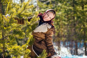 Young nice blond woman hold pine branches. Girl clothed shawl and sheepskin coat. Sunny winter day. National suit.