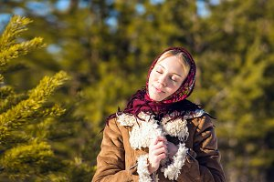 Young nice blond woman around pine branches. Girl clothed shawl and sheepskin coat. Sunny winter day. Russian national suit. She closed her eyes with pleasure