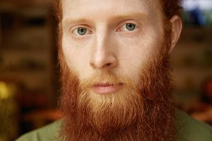 Human emotions and feelings. Headshot of attractive unhappy young redhead student with freckles and healthy clear skin looking at camera with sad, upset or disappointed expression on his face