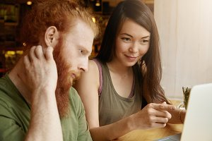 Portrait of young brunette female teacher pointing at screen of laptop computer, explaining new grammar topic to her perplexed redhead grown-up student during their English lesson at coffee shop