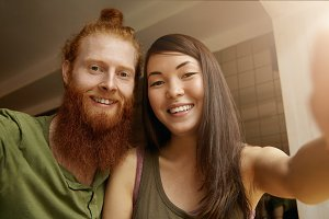 Young good-looking hipster man wearing casual shirt posing together with his best female friend with long dark hair while taking self portrait using gadget or electronic device sitting at restaurant