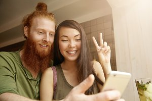 Portrait of hipster with red beard using generic mobile phone for videoconferencing with friends online together with her girlfriend showing peace gesture, smiling with happy look. Film effect