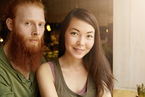Headshot of attractive student with red beard hugging his charming girlfriend wearing casual tank top, posing isolated against cafe interior background with copy space for your advertisement