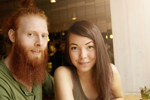 Two friends spending nice time together, having lunch at cafe. Pretty girl with cute smile and happy look sitting next to her hipster boyfriend with long red beard and blue eyes. Love and friendship