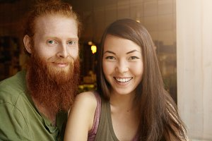 Portrait of happy beautiful couple: young redhead man embracing his attractive wife with long dark hair, looking and smiling at camera, posing against blurred interior background of restaurant