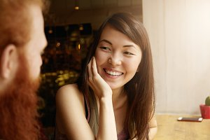 Close up portrait of good-looking brunette Asian female journalist having interview with popular male food blogger, sitting at conceptual coffee shop, smiling, having fun, looking happy and carefree