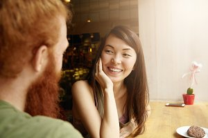 Selective focus. Cropped shot of two friends talking to each other sitting at loft cafe, ordering cookies. Young Asian woman with shy smile looking at her Caucasian companion with true interest