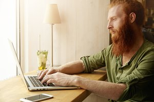 Young hipster with long red beard typing on keyboard of his laptop, surfing Internet, using wi-fi at coffee shop, sitting at table with cell phone with copy space for your text or promotional content