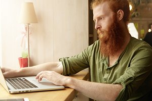 Profile of handsome redhead Caucasian student working on his diploma work on laptop computer, looking for information on Internet with serious concentrated expression, holding finger on touchpad