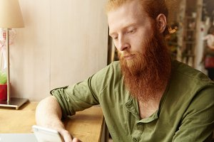 Headshot of young redhead male wearing green casual shirt, holding generic cell phone, browsing Internet and chatting with friends on electronic device, sitting against cafe interior background
