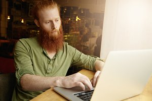 People and lifestyle concept. Young stylish guy with red hair and long beard in casual clothes sitting at loft cafe near window playing online games on his notebook, waiting for his friends to come