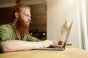 Portrait of redhead bearded white freelancer with trendy hair knot sitting in front of window at table typing on his laptop, working online, checking e-mail, looking serious and concentrated