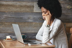 African female freelancer thinking on ideas for her new project, using laptop at co-working cafe, resting her elbow on wooden table, looking with thoughtful expression at screen. Visual effects