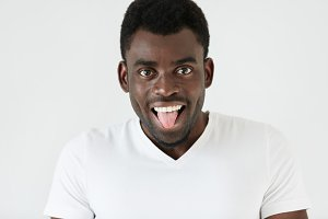 Human face expressions and emotions. Body language. Cheerful funny young African man wearing white T-shirt having fun, making faces, showing tongue to viewers, teasing them, spending free time indoors
