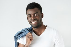 People and lifestyle concept. Happy African student dressed in casual white T-shirt looking at camera with happy expression on his face, holding denim jacket over his shoulder, ready to go for walk