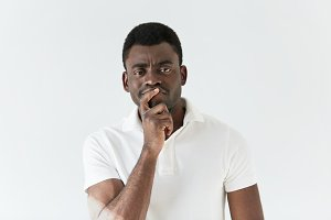 Dark-skinned male with mistrustful look posing against white concrete wall. Good-looking African man dressed in white T-shirt, looking with thoughtful skeptical expression, holding hand on his chin