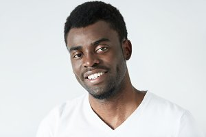 Headshot of attractive young African man smiling showing his white teeth with cheerful and happy expression, relaxing indoor against white studio wall background with copy space for your information