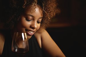 Close up shot of black girl with Afro hairstyle and healthy shiny skin sitting at bar, drinking red wine. Attractive woman with cute flirting smile, looking down while having date at restaurant
