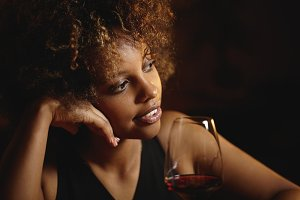 Fashionable African young lady with curlly hair at lounge bar, chilling, sitting at table with glass of red wine, resting her head on hand, looking thoughtful, dreaming and smiling mysteriously
