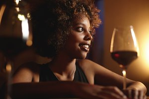 Selective focus. Profile portrait of attractive elegant dark-skinned female with Afro hairstyle sitting at restaurant table holding glass of red wine, looking away with happy mysterious smile