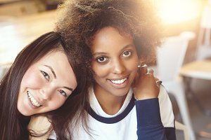 Portrait of two beautiful women of different ethnicities sitting at cafe, hugging and having fun. Attractive brunette Asian woman embracing her stylish African best friend with Afro hairstyle