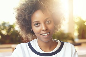 Flare sun. Close up shot of young good-looking dark-skinned female with Afro haircut wearing T-shirt, looking and smiling at camera. Happy girl with white teeth spending her free time indoors