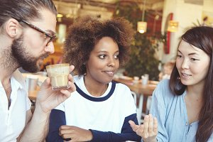 Three people of diverse races having conversation at cafe: Caucasian man in spectacles drinking hot chocolate and African woman with Afro haircut listening to their Asian friend telling something