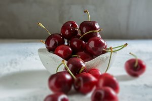 Cherries in white bowl, rustic textu
