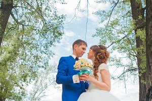 bride and groom standing  hugging on the background of trees