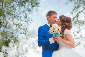 bride and groom kissing on the background of trees