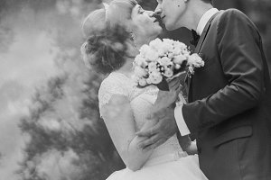black and white photo of bride  groom kissing in a forest