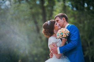 young bride and groom kissing on the background of the forest