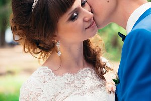 young bride and groom kissing on the background of the forest the road