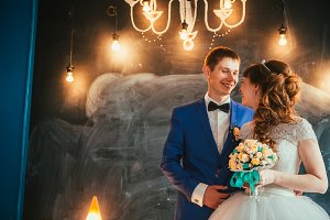 bride and groom in the interior of the studio are on the background wall