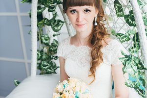 Portrait of a young happy bride in studio